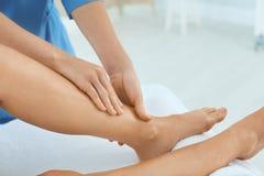 Woman receiving leg massage in wellness center. Closeup stock image
