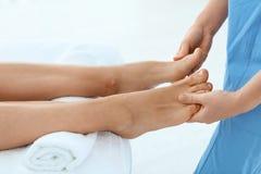 Woman receiving leg massage in wellness center. Closeup stock photography