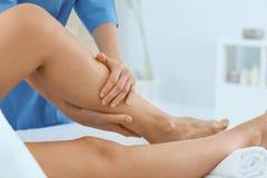 Woman receiving leg massage in wellness center. Closeup royalty free stock image