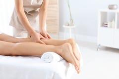 Woman receiving leg massage in wellness center. Closeup stock photo