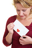 Woman receiving love letter. Happy woman holding a love letter in her hand Royalty Free Stock Photos