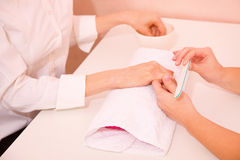 Woman receiving manicure treatment Stock Images