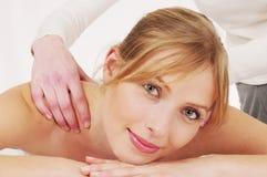Woman receiving a massage. Beautiful blond woman receiving a relaxing massage stock image