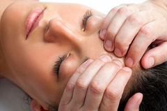 Woman receiving massage on forehead. Stock Photos