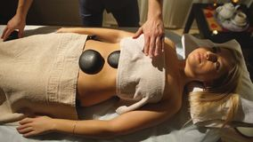 Woman receiving a massage with hot stone in a spa center stock footage