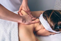 Woman receiving massage on shoulders in clinical center Stock Photo