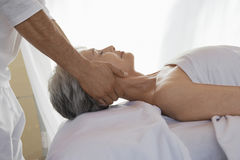 Woman Receiving Massage. Side view of a senior woman receiving massage at spa stock photo