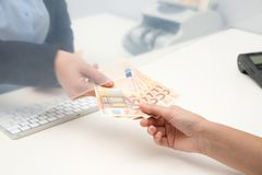 Woman receiving money from teller at cash department window. Closeup royalty free stock photography