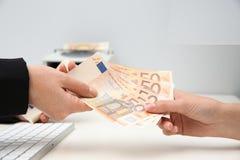 Woman receiving money from teller at cash department window. Closeup stock image