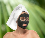 Woman receiving a mud mask on the white background. Stock Photo