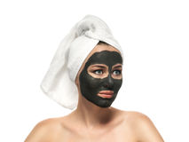 Woman receiving a mud mask on the white background. Stock Image