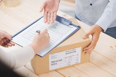 Woman receiving package from a delivery man Stock Photo