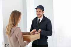 Woman receiving package from delivery man Stock Image