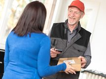 Woman receiving package from delivery man. Woman receiving package from smiling delivery man Royalty Free Stock Images