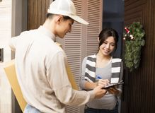 Woman receiving package from delivery man Royalty Free Stock Photography