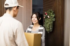 Woman receiving package from delivery man. Young women receiving package from delivery man Royalty Free Stock Images