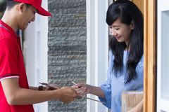 Delivery man delivering box. Woman receiving a package at home from a delivery guy Royalty Free Stock Photo