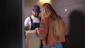 Woman receiving parcel at home from delivery man