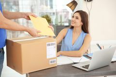 Woman receiving parcels from courier Stock Photos