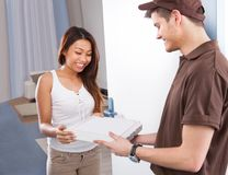 Woman receiving pizza from delivery man Royalty Free Stock Images