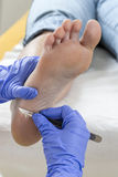 Woman receiving podiatry treatment- podiatrist chiropodist cleaning womans feet Royalty Free Stock Image