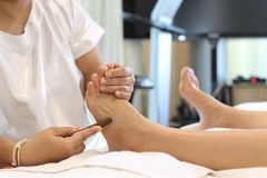 Woman receiving a Reflexology foot massage Stock Image