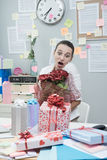 Woman receiving a romantic surprise at work. Stock Photo
