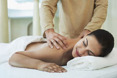 Woman Receiving Shoulder Massage By Masseuse. Relaxed young women receiving shoulder massage by masseuse at spa Stock Photo