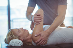 Free Woman Receiving Shoulder Therapy From Physiotherapist Royalty Free Stock Images - 74514889