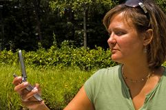 Woman Receiving Text Message. Woman outdoors receiving or sending a text message on her cellphone Stock Photo