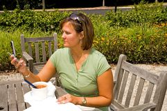 Woman Receiving Text Message - 2. Woman outdoors receiving or sending a text message on her cellphone stock photography