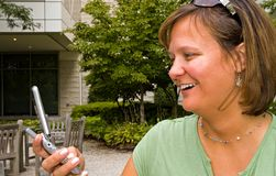 Woman Receiving Text Message - 3. Woman receiving a text message on her cellphone outdoors Stock Photography