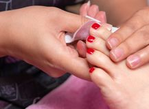 Woman receiving toenail pedicure service by pedicurist at nail salon. Beautician coating red gel color toenail at nail salon. Woman receiving toenail pedicure stock images