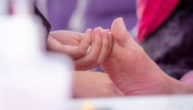 Woman receiving toenail pedicure service by professional pedicurist at nail salon. Beautician file nail pedicure at nail and spa. Salon. Foot care and toenail stock images