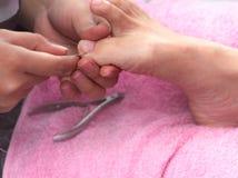 Woman receiving toenail pedicure service by professional  pedicurist at nail salon. Beautician file nail pedicure at nail and spa. Salon. Foot care and toenail stock photos