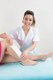 Woman receiving a waxing treatment on legs at spa. Stock Photos