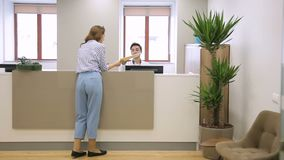 Woman at reception passes documents to man who sits talking on phone. Female employee passes folder with papers to male secretary, who is sitting at counter stock video footage