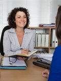 Woman receptionist and personal assistant is very serious. She is taking notices as a business woman Royalty Free Stock Photo