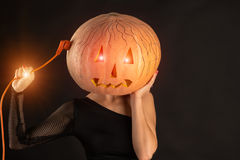 Woman recharges pumpkin head, concept of Halloween Stock Photography