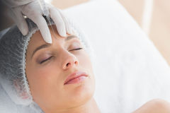 Woman recieving botox injection in forehead Stock Photos