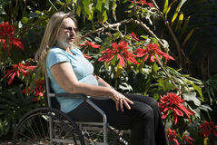 Woman Reclines in Wheelchair - Horizontal. Woman sits outdoors in a wheelchair alongside flowers looking ahead. Horizontally framed photo Stock Photography