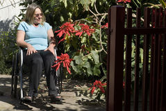 Woman Reclines in Wheelchair - Horizontal. Woman sits outdoors in a wheelchair alongside flowers looking to the side. Photo is taken from  the front Stock Image