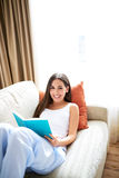 Woman reclining against orange cushion looking up smiling. Royalty Free Stock Image