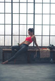 Woman reclining on bench selecting music in loft gym Royalty Free Stock Images