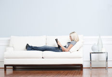 Woman Reclining on Couch With Book. Full length view of woman reclining on white couch and reading a book. Horizontal format Royalty Free Stock Image
