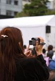 Woman recording an event. Woman using a prosumer digital handy-cam to record a show from the audience stock photo