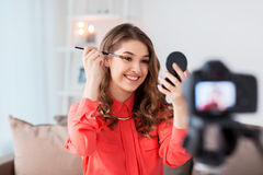 Woman recording eye makeup tutorial video at home. Blogging, technology, videoblog, makeup and people concept - happy smiling woman or beauty blogger with eye Royalty Free Stock Image