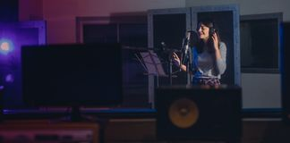 Woman recording a song in music studio Stock Image