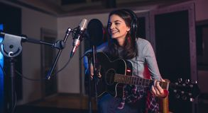 Woman recording a song in a professional music studio. Happy young woman recording a song in a professional music studio. Smiling female sitting on front of Stock Image