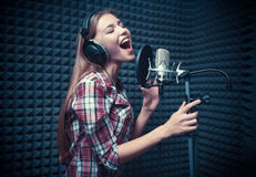 Woman in a recording studio. Young woman singing in a recording studio stock photo